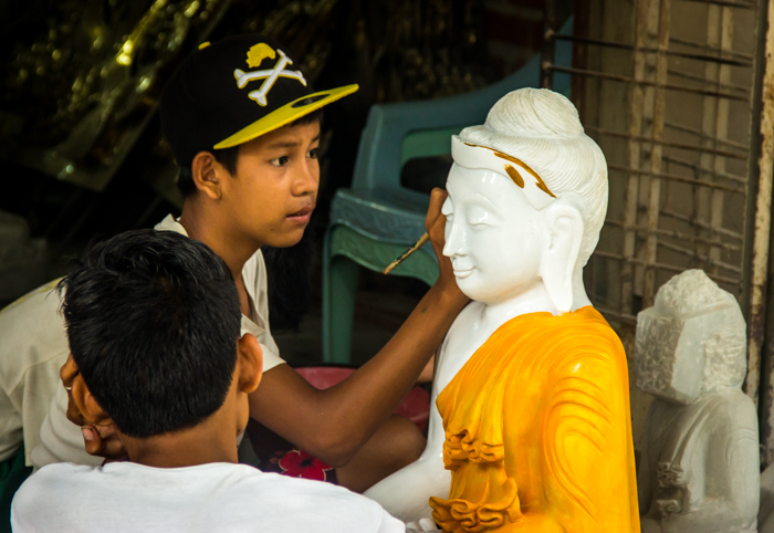 Painting. The final touch before the Buddhas get sent somewhere in Myanmar.