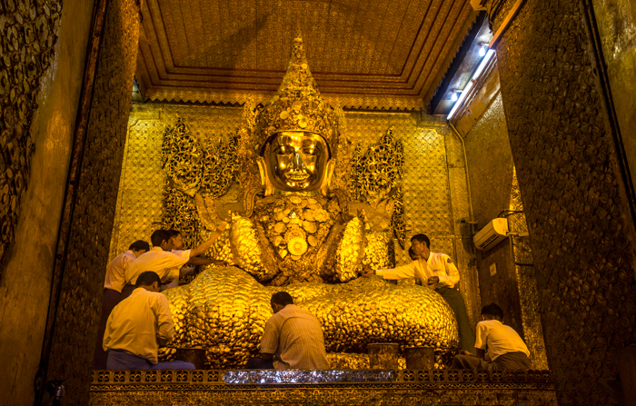 The Buddha being decorated some more.