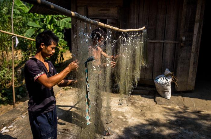 Fishermen fixing their nets on route Dong Van, Vietnam